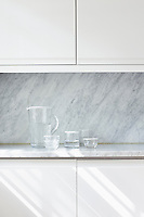Detailing in the minimal kitchen includes grey marble work tops and splash back
