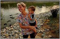 A grandmother laughs while holding her grandson. Ducks swimming in background.  Model released image can be used to illustrate many purposes.