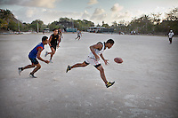 Young teenagers playing Aussie rule football...Nauru, officially the Republic of Nauru is an island nation in Micronesia in the South Pacific.  Nauru was declared independent in 1968 and it is the world's smallest independent republic, covering just 21 square kilometers..Nauru is a phosphate rock island and its economy depends almost entirely on the phosphate deposits that originate from the droppings of sea birds. Following its exploitation it briefly boasted the highest per-capita income enjoyed by any sovereign state in the world during the late 1960s and early 1970s..In the 1990s, when the phosphate reserves were partly exhausted the government resorted to unusual measures. Nauru briefly became a tax haven and illegal money laundering centre. From 2001 to 2008, it accepted aid from the Australian government in exchange for housing a Nauru detention centre, with refugees from various countries including Afghanistan and Iraq..Most necessities are imported on the island..Nauru has parliamentary system of government. It had 17 changes of administration between 1989 and 2003. In December 2007, former weight lifting medallist Marcus Stephen became the President.