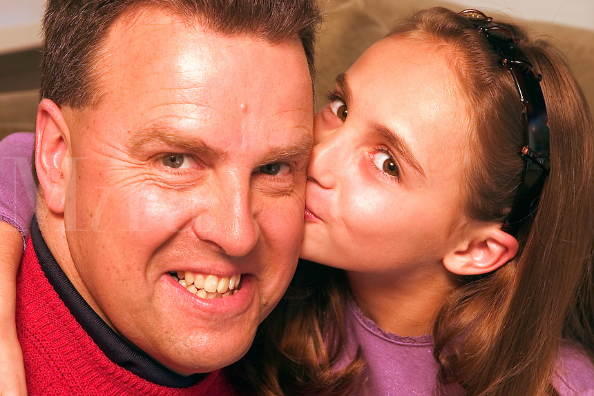 Girl hugging and kissing her dad.