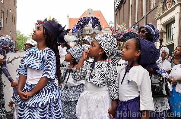 Nederland  Amsterdam - 2018.  Memre Waka optocht door de stad. Op 1 juni wordt in Amsterdam met de herdenkingstocht Memre waka de jaarlijkse Keti koti-maand geopend, die op 1 juli eindigt met de viering van de afschaffing van de slavernij (1 juli 1863). Deze mars wordt georganiseerd door stichting Eer en Herstel en vereniging Opo Kondreman, in samenwerking met onder meer NINSEE en de Black Heritage Tours. Deelnemers aan de tocht krijgen uitleg over huizen die met slavernij te maken hadden.  Foto mag niet in negatieve / schadelijke context gebruikt worden.   Foto Berlinda van Dam / Hollandse Hoogte.