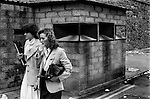 Derry, Northern Ireland. 1979<br /> Two smartly dressed women walking past a burnt out British Army check point at Butchers Gate, a gateway through the old city wall and into the commercial centre of Derry.