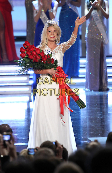 TERESA SCANLAN - Miss America 2011.Miss Nebraska Teresa Scanlan is named the Miss America 2011 at The Theater for the Performing Arts at Planet Hollywood Resort Hotel and Casino, Las Vegas, Nevada, USA, .15th January 2011..full length white dress sash winner crowned crown on stage one shoulder long maxi red roses flowers 3/4 hand waving .CAP/ADM/MJT.© MJT/AdMedia/Capital Pictures.