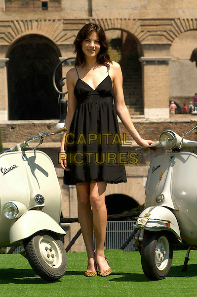 "MICHELLE MONAGHAN.Photocall for ""Mission Impossible 3"" at the Colosseum, Rome, Italy..April 24th, 2006                   .Ref: CAV.full length black dress vespa .www.capitalpictures.com.sales@capitalpictures.com.© Capital Pictures."