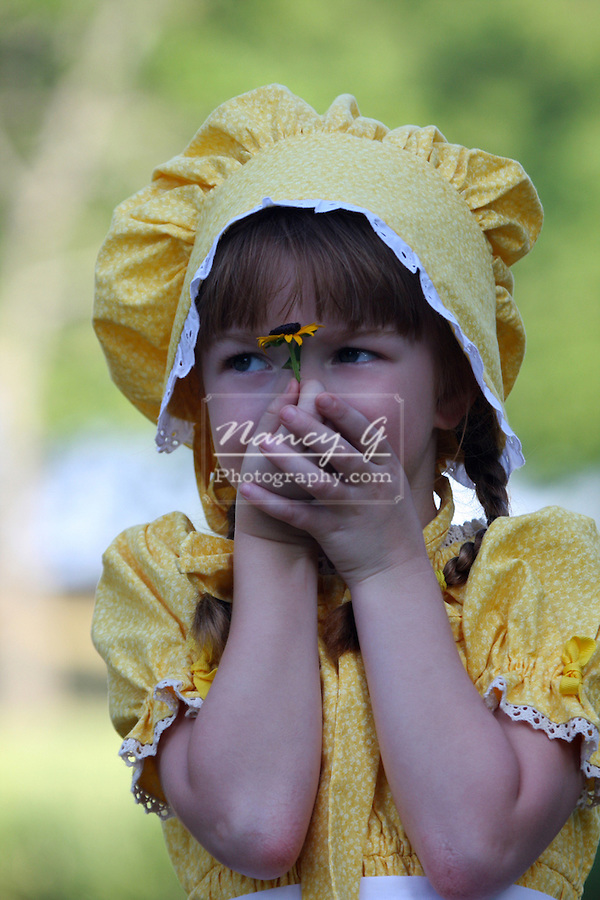 A young girl holding a flower up to her face