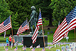 Memorial Day Ceremony at cemetary with American Flags, military sculpture and flags at grave sites
