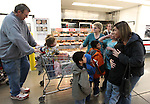 Vicki Kral, right, an assistant at Dayton Intermediate School, greets Merrill and Roberta Simon and their 13 children while shopping at Costco in Carson City, Nev., on Sunday, Dec. 18, 2011.  The Simons have adopted 21 special-needs children over the past 30 years..Photo by Cathleen Allison