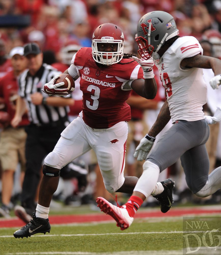 NWA Media/ANDY SHUPE - Arkansas running back Alex Collins (3) reaches to fend off Nicholls defensive back Josh Dewey during the third quarter Saturday, Sept. 6, 2014, at Razorback Stadium in Fayetteville