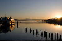 Washington State Ferry docked at sunrise at Anacortes, Washington, the Cascade Mountains in background.