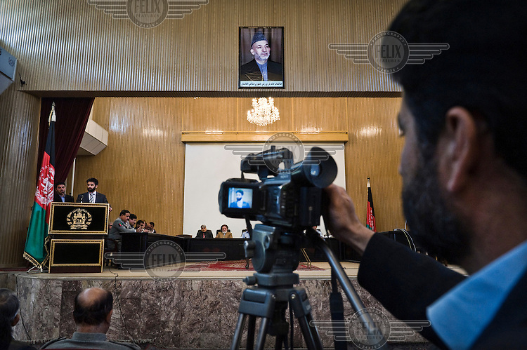 A press conference is recorded in Kabul. A portrait of President Hamid Karzai hangs from the wall above.