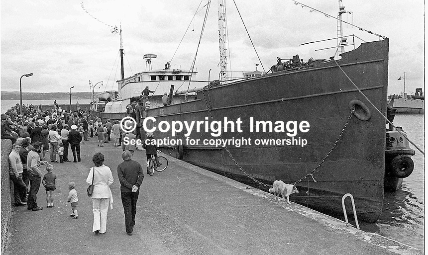 Sightseers at Carrickfergus Harbour, N Ireland, to see the departure of the UVF gun-running ship, Clyde Valley, to the breaker's yard. NI Troubles. Ref: 197408022<br /> <br /> Copyright Image from Victor Patterson, 54 Dorchester Park, <br /> Belfast, UK, BT9 6RJ<br /> <br /> t1: +44 28 9066 1296 (from Rep of Ireland 048 9066 1296)<br /> t2: +44 28 9002 2446 (from Rep of Ireland 048 9002 2446)<br /> m: +44 7802 353836<br /> <br /> e1: victorpatterson@me.com<br /> e2: victorpatterson@gmail.com<br /> <br /> www.victorpatterson.com<br /> <br /> Please see my Terms and Conditions of Use at www.victorpatterson.com. It is IMPORTANT that you familiarise yourself with them.<br /> <br /> Images used on the Internet must be visibly watermarked i.e. &copy; Victor Patterson within the body of the image and copyright metadata must not be deleted. Images used on the Internet have a size restriction of 4kbs and will be chargeable at current NUJ rates unless agreed otherwise.<br /> <br /> This image is only available for the use of the download recipient i.e. television station, newspaper, magazine, book publisher, etc, and must not be passed on to any third party. It is also downloaded on condition that each and every usage is notified within 7 days to victorpatterson@me.com<br /> <br /> The right of Victor Patterson to be identified as the author is asserted in accordance with The Copyright Designs And Patents Act (1988).