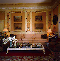 The wall of the drawing room has been decorated with trompe l'oeil panels which frame a collection of paintings