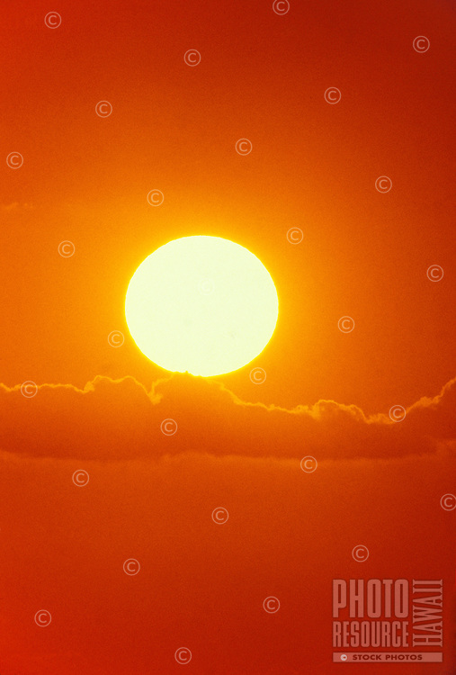 Dramatic photo of a dazzling white-hot sun resting above a cloud band shaped like an open hand and completely surrounded by deep orange hues.