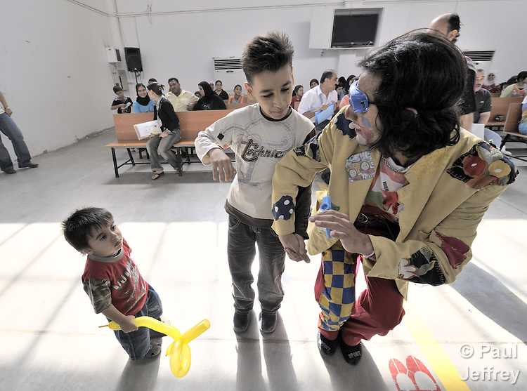 Rahman Aidi Mashoof, a member of the Happy Family Team for Childhood Peace, helps Iraqi refugee children have fun while they and their families wait to be registered at an intake center of the United Nations High Commissioner for Refugees in Douma, on the outskirts of Damascus, Syria. More than one million Iraqi refugees may reside in Syria, and the UN provides assistance with education, food, housing, and a variety of other services. The Happy Family Team has three members, all Iraqi refugees themselves.
