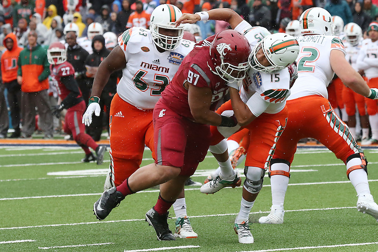 Destiny Vaeao, Washington State University defensive lineman, pressures the quarterback during the Hyundai Sun Bowl game against the Miami Hurricanes in El Paso, Texas, on December 26, 2015.  In a game that could have been named the Snow Bowl instead of the Sun Bowl, WSU took a 20-7 lead in to halftime and then held off a Miami fourth quarter rally to win their first bowl game since the 2003 Holiday Bowl, 20-14.