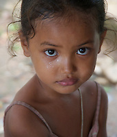 Portrait of a little girl during a tropical rain shower rural area near Battambang Cambodia