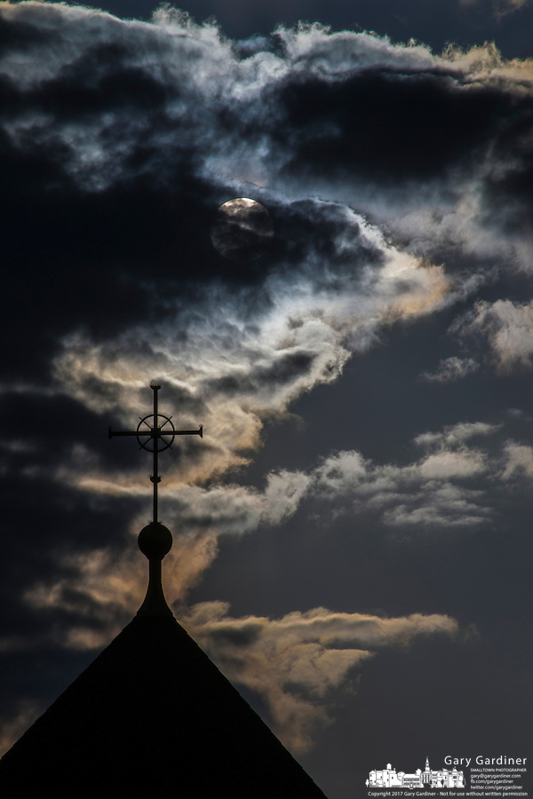 Clouds and the sun near sunset on Good Friday over St. Paul Catholic the Apostle Catholic Church in Westerville Ohio.