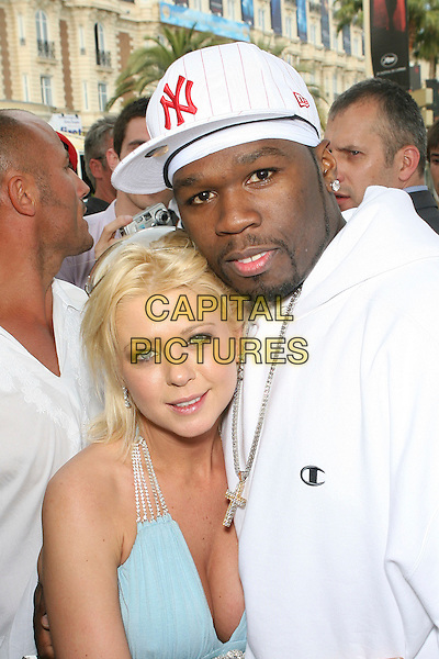 TARA REID & 50 CENT (CURTIS JACKSON).Saying hello to 50 Cent after he departs the Nikki Beach Gift Suite held near the sands at the Carlton Hotel after picking up luxury items including Caribbean Escapes Getaways, Leblon Cachaca Rum, and Frederic Fekkai treatments: 2006 Cannes International Film Festival, France, day 7.  .May 22nd, 2006.Photo: Zach Lipp/AdMedia/Capital Pictures.Ref: ZL/ADM.half length blue top white baseball cap hat cleavage.www.capitalpictures.com.sales@capitalpictures.com.© Capital Pictures.