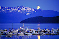 An eclipsing moon sets over the Auke Bay harbor, Juneau, Alaska (Southeast Alaska) Pleasure craft and fishing boats use the harbor. Juneau Alaska, Auke Bay Harbor.