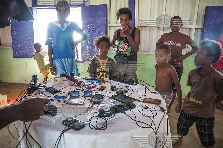 Children guard their and their parent's phones and tablets while they are being charged from the community generator. After Cyclone Pam hit Vanuatu on 13 March 2015, many villages were left without electricity. Some village communities run small generators that their residents can charge mobile phones so to be able to call their relatives in case of emergency.