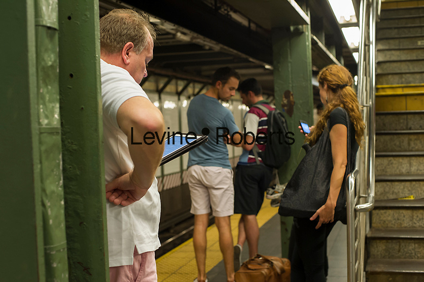 While waiting for the subway at the Times Square subway station in New York, a commuter uses his tablet computer, left, while another commuter, right, uses her cellphone.  (© Frances M. Roberts