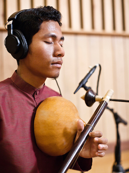 Classical Wedding musician Sinat plays his Kse Diev (instrument)  at the Cambodian Living Arts studio in Phnom Pehn , Cambodia...The music Sinat plays, plaing kaa boran or classical wedding music, is steeped in his country's history, and together with the Angkor Temples is one of the few remaining vestiges of ancient Khmer culture. While this form of traditional music is one of Cambodia's oldest and most-loved, today only a handful of musicians from Siem Reap and Takeo provinces know how to play it. ..Cambodian Living Arts works to support the revival of traditional Khmer performing arts and to inspire contemporary artistic expression. CLA supports arts education, mentorship, networking opportunities, education, career development, and income generating projects for master performing artists who survived the Khmer Rouge as well as the next generation of student artists.