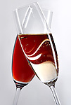Two crossed wine glasses with champagne and red wine romantic concept