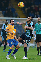 Wycombe Wanderers captain Paul Hayes lifts the ball over his head watched by Mansfield Town's Ryan Tafazolli during the Sky Bet League 2 match between Mansfield Town and Wycombe Wanderers at the One Call Stadium, Mansfield, England on 31 October 2015. Photo by Garry Griffiths.