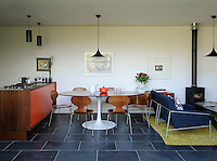 An open-plan kitchen/dining/living room with Scandinavian Modern style in a homely, contemporary space. The wooden kitchen units were handmade in water-resistant iroko with orange laminate on the door fronts and chamfered edges. Eames dining chairs surround an Arkana rosewood table in the dining area, set off by the  Brazilian black slate flooring.