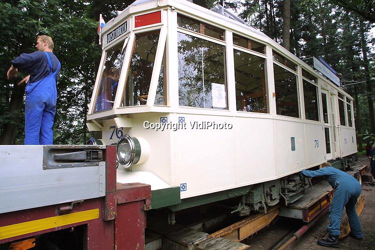 Foto: VidiPhoto..ARNHEM - In het Openluchtmuseum in Arnhem is maandag een 20 ton zware tram op een dieplader getakeld voor transport naar Rotterdam. De wielen van de witte GETA 56, een replica van trams die tot 1944 in het centrum van Arnhem reden, moeten geherprofileerd worden. De zogenoemde flensen, opstaande randen die er voor zorgen dat de tram op de rails blijft, zijn weggesleten. Vrijdag keert de tram weer terug in het museum.