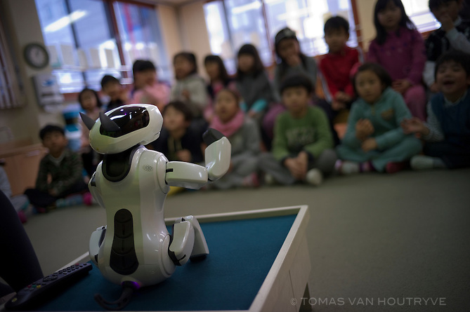 Nursery school children interact with a robotic puppy named Genibo in Seoul, South Korea on Feb. 2, 2012. Genibo keeps students occupied with learning activities and helps teachers deal with larger class sizes. With Genibo the students follow a lesson book that was developed by the state education authorities. The robot responds to touch, sound, movement and a remote control.