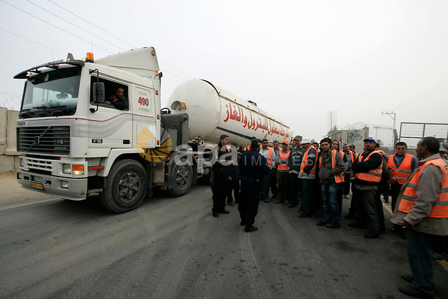 Palestinian workers stand next to an oil truck in the Palestinian Rafah border crossing while the oil trucks are preparing to go to bring fuel from crossing Karem Salem Israeli , in the southern Gaza Strip on November 29, 2010. Photo by Abed Rahim Khatib