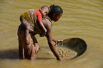 MADAGASCAR, region Manajary, town Vohilava, small scale gold mining, women panning for gold at river ANDRANGARANGA, mother carry her child on the back during the work / MADAGASKAR Mananjary, Vohilava, kleingewerblicher Goldabbau, Frauen waschen Gold am Fluss ANDRANGARANGA, Mutter traegt ihr Kind bei der Arbeit auf dem Ruecken