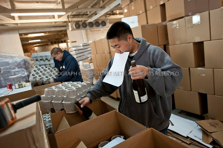 10/6/2010--Seattle, WA, USA..Hana Paik, 23, an employee at Garagiste, helps to pack wine in the company's warehouse to be shipped from Seattle's Sodo district...©2010 Stuart Isett. All rights reserved.