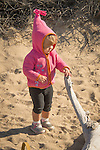 Toddler girl child on beach looking at driftwood.