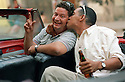 Driven by Necessity-Friends- Two friends in a 1952 Plymouth enjoy a beer and a smooch in Old Havana Cuba