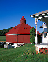 Pepin County, WI<br /> Morning light on an octagonal red barn and corner post of a farm house porch
