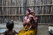 Maina Devi plays with her 3 month old daughter, Priya while her son, Pradeep (2) looks on in the courtyard of their hut in Bhelaiya village in Raxaul, Bihar, India.