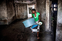 A woman carries a plastic basin inside the former Grand Hotel building. Once a luxury destination for the wealthy and the continent's biggest hotel, the building is now a concrete shell and home to about 6,000 squatters. Those unable to occupy one of the rooms sleep in the corridors, basements and even on the roof of the building.