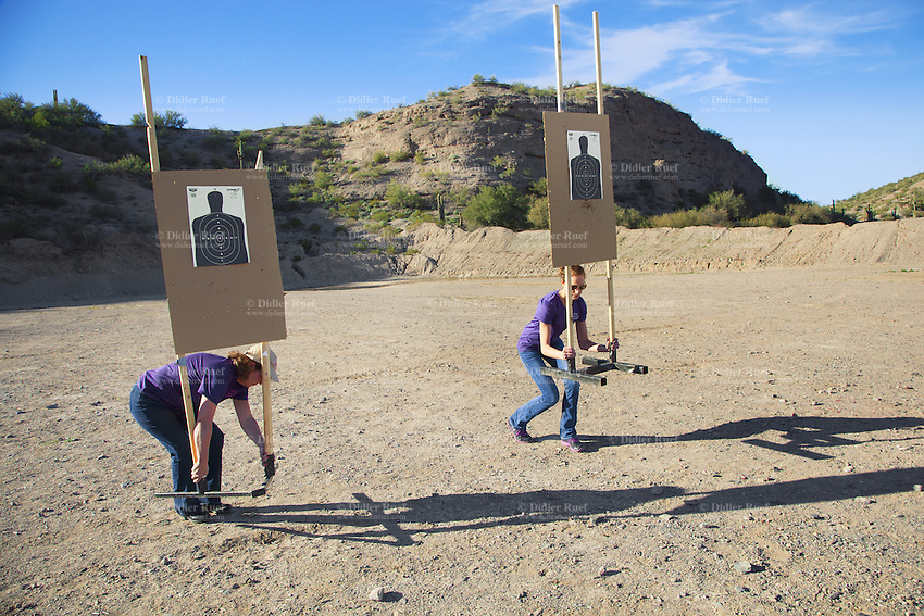 "USA. Arizona state. Peoria. Peoria is distant 50 km from Phoenix. Cowtown Shooting Range. Cowtown is a semi-private outdoor shooting range and firearms training facility. Carrie Lightfoot (L) and her colleague Ashley Suris are setting the targets. Both women came to train their shooting skills with various firearms. Carrie Lightfoot is the founder and CEO of ""The Well Armed Woman. Where the Feminine and Firearms Meet"" which sell online resources for women gun owners. A firearm is a portable gun, being a barreled weapon that launches one or more projectiles often driven by the action of an explosive force. Most modern firearms have rifled barrels to impart spin to the projectile for improved flight stability. The word firearms usually is used in a sense restricted to small arms (weapons that can be carried by a single person). The right to keep and bear arms is a fundamental right protected in the United States by the Second Amendment of the Bill of Rights in the Constitution of the United States of America and in the state constitutions of Arizona and 43 other states. 28.01.16 © 2016 Didier Ruef"