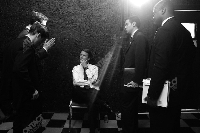 After a rally in Denver, Colorado, former Sen. John Edwards is briefed by his staff before a series of TV interviews..July 23, 2004..