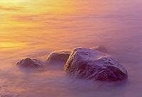 Waves of Lake Winnipeg crashing on shoreline rocks at sunrise<br /> Hecla Provincial Park<br /> Manitoba<br /> Canada