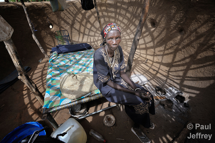 Bruna Maloal, a 63-year old Roman Catholic catechist, sits in her simple home in Abyei, a town at the center of the contested Abyei region along the border between Sudan and South Sudan. Her home was looted and burned in 2011 when soldiers and militias from the northern Republic of Sudan swept through the area, chasing out Maloal and tens of thousands of others. Maloal and a handful of other residents returned to the town in 2012 after northern combatants withdrew. She has constructed the framework for a thatched roof, but has yet to cut the grasses needed for the thatching. Although Ethiopian peacekeepers patrol the region, renewed attacks by northern-backed Misseriya militias in 2013 have Maloal and others worried. The African Union has proposed a new peace plan, including a referendum to be held in October 2013, but it has been rejected by the Misseriya and Khartoum. The Catholic parish of Abyei, with support from Caritas South Sudan and other international church partners, has maintained its pastoral presence among the displaced and assisted them with food, shelter, and other relief supplies. Yet the parish priests have not officially returned to Abyei, remaining with most Abyei residents in Agok, some 25 kilometers to the south. Every Sunday a priest comes to celebrate Mass in Abyei, with church members gathering under a tree outside the desecrated sanctuary.