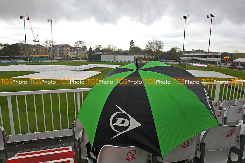 A spectator shelters under an umbrella as rain delays the start of Essex CCC vs Northamptonshire CCC, Specsavers County Championship Division 2 Cricket at the Essex County Ground on 25th April 2016