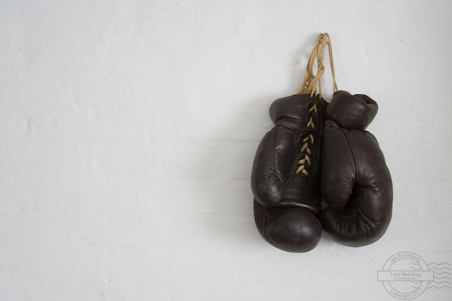 Old boxing gloves, hanging on a wall. These gloves used to belong to the danish boxer Tom Bogs.