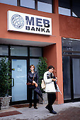 Sarajevo, Bosnia and Herzegovina. The entrance of the MEB Banka (Micro Enterprise Bank); people with umbrellas.
