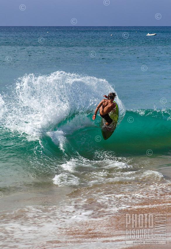 A skimboarder doing a 360-degree turn at Ka'anapali Beach, Maui.