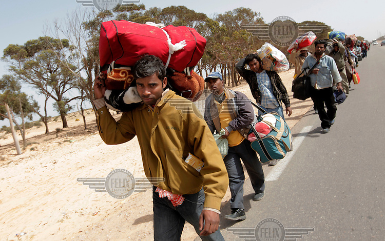 Thousands of refugees from Bangladesh walk from the border to a camp in the Tunisian desert. Tens of thousands of people, mainly migrant workers, fled unrest in Libya and crossed the border into Tunisia. Some slept in the open for several days before being processed.  At the same time forces loyal to Col. Gaddafi fought opposition forces in various parts of the country.