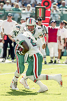 MIAMI, FL - DEC 19, 1999: Quarterback Dan Marino, #13, hands off to running back Autry Denson, #21, as the  Miami Dolphins defeat the San Diego Chargers 12-9 at Joe Robbie Stadium, in Miami, FL. (Photo by Brian Cleary/www.bcpix.com)
