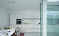 The L-shaped kitchen is furnished with an oval table and has units the length of one wall